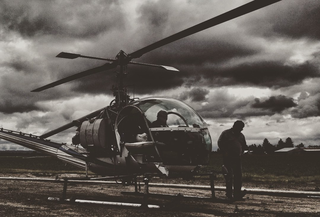 Black and white photo of helicopter and pilot on the ground
